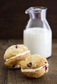 Cranberry-orange Whoopie Pies, filled with white chocolate cream, in front of a milk bottle