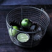 Limes in a cake tin in a bucket