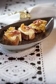 Crostini topped with bacon and Vacherin cheese
