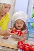 A mother and daughter with tomatoes and pizza dough