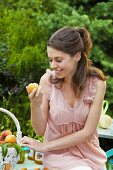 Young woman biting into a freshly picked peach