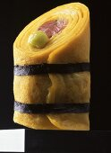 A rolled crepe with tuna fish, wasabi, tied with seaweed
