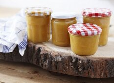 Four jars of quince jam on a wooden disc