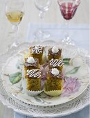 Several pieces of poppy seed cake on a plate with a decorative rose design