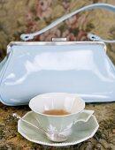 Tea cup in front of a handbag