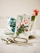 Post card with a picture of a rose on a tea table