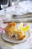 Fried mussels in beer batter with lemon wedges
