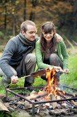 Pärchen mit Steckerlfisch an Feuerstelle sitzend