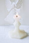 A white candle with a folded paper angel behind it