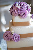 A three tier wedding cake with purple marzipan roses