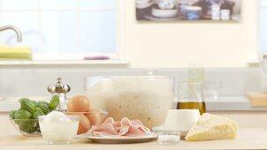 Ingredients for calzone (ricotta, parmesan, Parma ham, mozzarella, eggs, pizza dough)