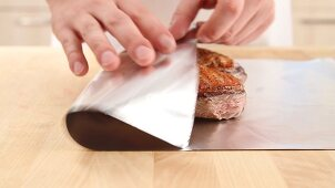 Fried duck breast being wrapped in aluminium foil