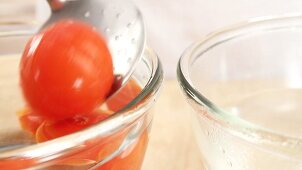 Tomatoes being removed from a bowl of hot water and placed into a bowl of cold water