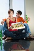 Young couple with beer and pizza