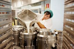 A woman pouring milk into a container in a commercial kitchen