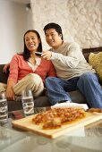 Couple on sofa watching television with pizza and drinks