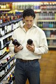Man comparing two bottles of wine in a supermarket
