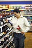 Man with bottle of wine and red roses in a supermarket