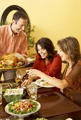 Man Holding Carved Thanksgiving Turkey While Women Serve Themselves at Thanksgiving Table
