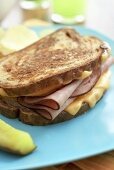 Whole Grilled Ham and Cheese Sandwich with Chips and Pickle