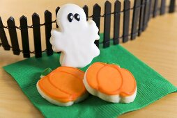 Two Pumpkin Cookies and a Ghost Cookie with Black Fence for Halloween
