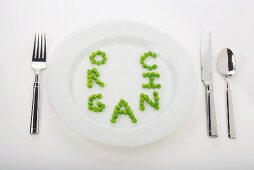 The Word Organic Spelled Out in Peas on a White Dinner Plate