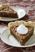 Two pieces of pecan pie with cream