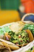 Tortilla Chip in a Bowl of Fresh Guacamole