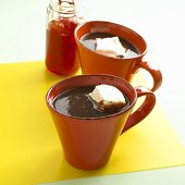 Two Mugs of Hot Chocolate with Marshmallows; Jar of Cherries