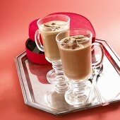 Two glass mugs of hot chocolate with pecan nuts
