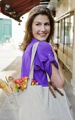 Woman Holding a Cloth Bag Filled with Bread and Flowers; Paris France