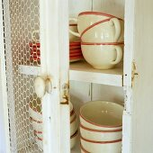 Crockery with coloured edges in a white wooden cupboard with an open door