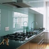 A kitchen with stainless steel cupboards and a glass rear wall