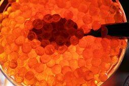 Salmon caviar in dish with spoon (overhead view)