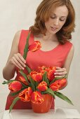 A woman with a bunch of red tulips