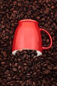 A coffee mug sinking into a pile of coffee beans