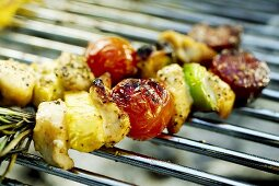 Two vegetable kebabs lying on a barbecue