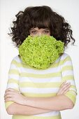 Woman with lettuce in front of her mouth
