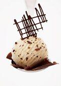 A scoop of stracciatella ice cream with chocolate flakes