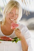 Blond woman eating watermelon