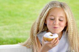 Blond girl eating doughnut