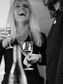Man with wine glass, laughing woman with glass of sparkling wine