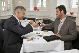 Two businessmen clinking glasses of wine