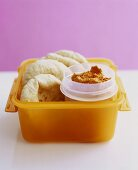 Pita bread with hummus in a plastic box