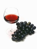 Glass of Red Wine with Purple Grapes
