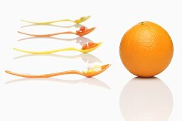 Spoons with vitamin tablets and an orange