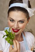 A retro-style girl holding fresh mint leaves