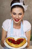 A retro-style girl holding a heart-shaped puff pastry cake