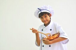 A boy dressed as a chef holding a mixing bowl and a wooden spoon