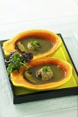 Green tea soup in papaya shells with meat balls (Asia)